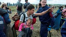 A migrant is stopped by police in Hungary with an infant