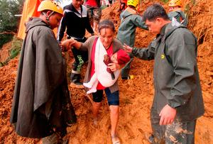 Rescuers help a mother and her child after landslides in Itogon township in Benguet province in the northern Philippines. Photo: Jayjay Landingin/AP