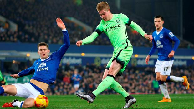 Manchester City's Kevin De Bruyne takes a shots while being challenged by Everton's John Stones (left) during the match at Goodison Park. Photo:  Martin Rickett/PA.