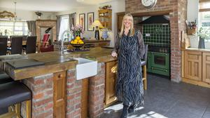 Mary Keane in the 40-feet-long kitchen/living/dining room, designed by her architect father, which she added to her cottage as the family grew. Everything in the room is authentic, and much of it is salvaged, including the bricks surrounding the range and the sleepers on the island top. The slate floor is from Slane, and everywhere there are examples of Irish craft including the Thomas Diem jug for the flowers and the John Rocha bowl holding the oranges. Photo: Tony Gavin