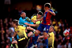 Watford goalkeeper Heurelho Gomes (second from left) punches the ball clear under the challenge from Dwight Gayle