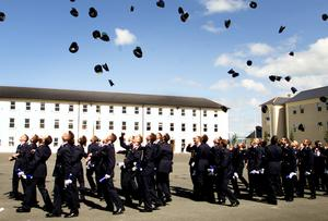Garda graduates celebrate by throwing the caps in the air after graduating from the garda training college.