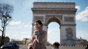 Precaution: A woman wearing a mask walks near the Arc de Triomphe in Paris as France looks to tackle the virus. Photo: REUTERS