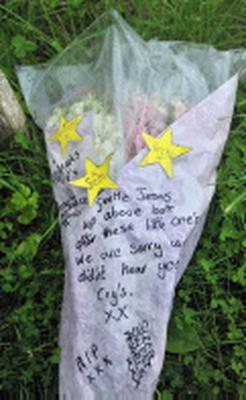 A floral tribute near the entrance to the forest on Pontesbury Hill near Shrewsbury, near to the scene where the bodies of three children were found.