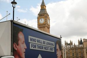 An advertising van with images of Britain's Prime Minister David Cameron and leader of the opposition Labour Party Ed Miliband drives around Parliament Square, central London, Britain. REUTERS/Phil Noble