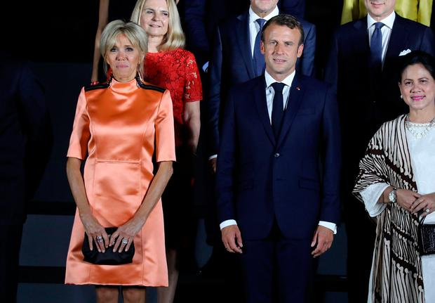 France's President Emmanuel Macron (C) and his wife Brigitte (L) pose for a group photo during the G20 Summit in Osaka on June 28, 2019. (Photo by Dominique JACOVIDES / POOL / AFP)
