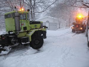 A Marquette Department of Public Works snow-plow truck gets a tow from a front-end loader while snow falls in Marquette, Mich. (AP Photo/The Mining Journal, Ryan Jarvi)