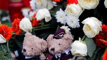 Two teddy bears dressed in the uniforms of a Germanwings pilot and a flight attendant sit in the centre of a wreath outside the Germanwings headquarters at Cologne-Bonn airport (REUTERS/Wolfgang Rattay)