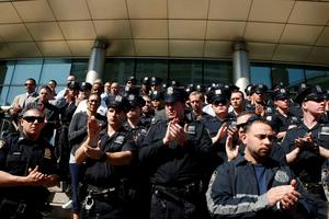 NYPD officers claps after listen to the Police Benevolent Association President Pat Lynch at the steps of the Queens criminal court in New York May 3, 2015. REUTERS/Eduardo Munoz