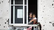 A mother holds her child while looking out from her Gaza City apartment, which has been badly damaged from artillery fire