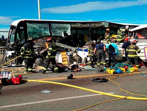 Firefighters assist victims after a crash between a bus and a tour vehicle on the Aurora Bridge in this picture from the Seattle Fire Department, in Seattle