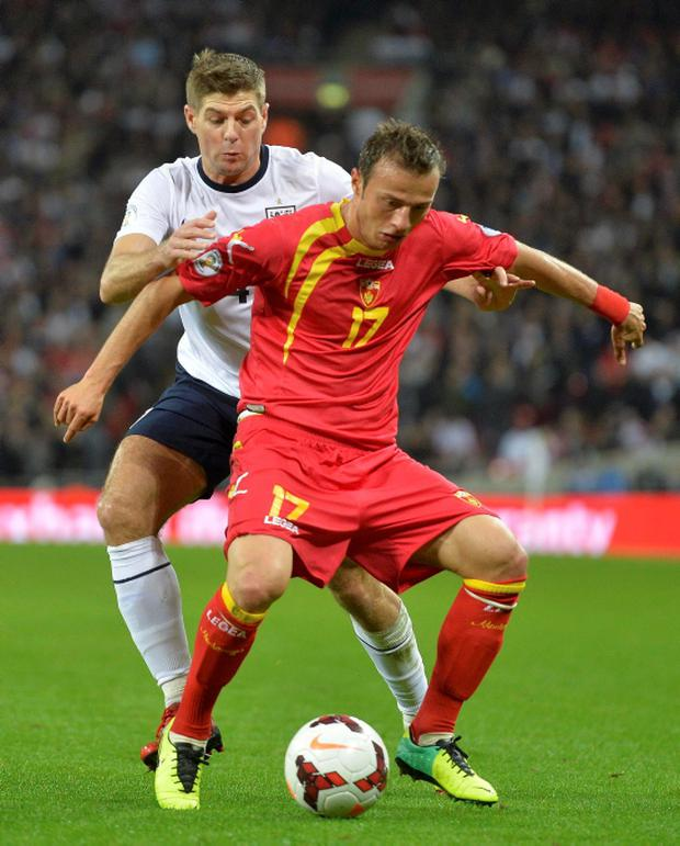 England's Steven Gerrard and Montenegro's Elsad Zverotic fight for the ball during their 2014 World Cup qualifying soccer match at Wembley Stadium