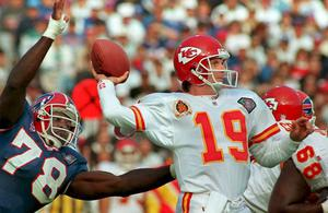 Kansas City Chiefs quarterback Joe Montana (19) preparing to pass against the rush of Buffalo Bills Bruce Smith (78) in 1994.  Montana led the San Francisco 49ers to four Super Bowl victories in the 1980s before finishing his career at the Chiefs .  Photo credit: JEFF HAYNES/AFP via Getty Images