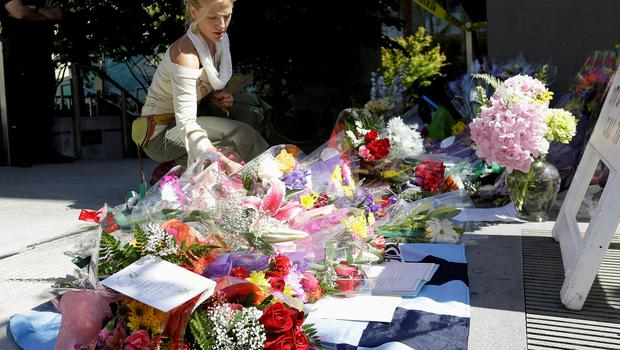 Toni Mikulka places flowers at a makeshift memorial for victims of a balcony that collapsed in Berkeley, Calif., Tuesday, June 16, 2015. (AP Photo/Jeff Chiu)