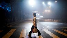 Ground zero: A woman walks on a foggy street in Wuhan, the Chinese city hit the hardest by the coronavirus. Photo: REUTERS/Aly Song