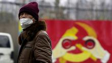 A man wears a mask as he walks past a mural showing a modified image of the Chinese Communist Party emblem in Shanghai, China after the country is hit by an outbreak of the new coronavirus