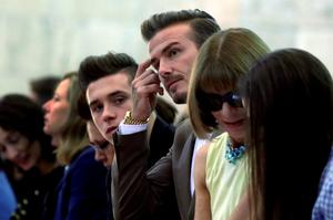 David Beckham, center, husband of designer Victoria Beckham, and their son Brooklyn Beckham, sit in the front row as they wait for her Spring 2016 collection to be modeled during Fashion Week, in New York, Sunday, Sept. 13, 2015. Seated at right is Anna Wintour, editor-in-chief of American Vogue. (AP Photo/Richard Drew)