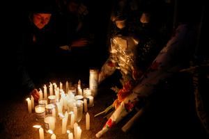 People lay candles at a makeshift memorial during a vigil for the seven children who died early Saturday morning during a home fire in the Midwood neighborhood of the borough of Brooklyn in New York March 22, 2015. REUTERS/Shannon Stapleton