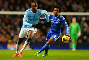 Willian of Chelsea marshalls Yaya Toure of Manchester City