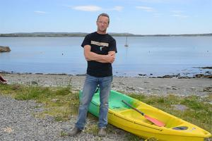 Mark O'Mahony with the kayak and broken paddle which he used to rescue three men from the sea when their dinghy capsized