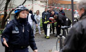 Firefighters carry a victim on a stretcher at the scene after a shooting at the Paris offices of Charlie Hebdo, a satirical newspaper, January 7, 2015. REUTERS/Jacky Naegelen