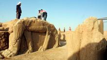 A file picture taken on July 17,  2001 shows Iraqi workers cleaning a statue of winged bull at an archeological site in Nimrud