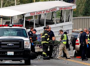 Personnel remove a victim's body from the scene of a crash between a Ride the Ducks vehicle and a charter bus on Aurora Bridge in Seattle