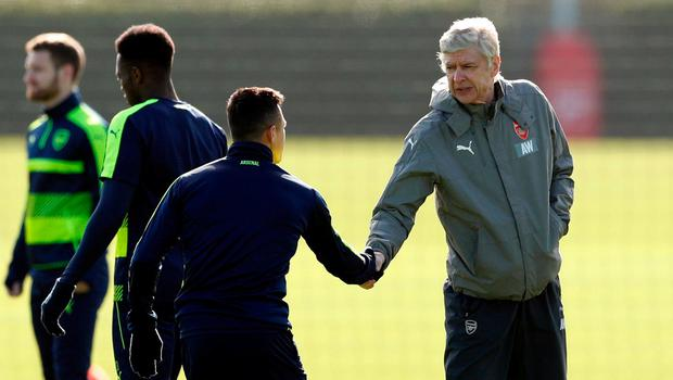 Arsene Wenger shakes hands with Arsenal's Alexis Sanchez during training today