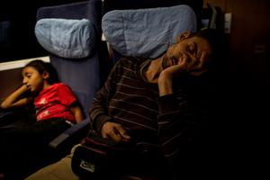 Ihab, 30 (R), a Syrian migrant from Deir al-Zor, sleeps beside his daughter Yasmine, 6, inside a train as they head to meet his parents in Lubeck, Germany, in this September 18, 2015 file picture. REUTERS/Zohra Bensemra/Files