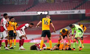 "Players reacts after Arsenal's David Luiz (left, floor) clashes heads with Wolverhampton Wanderers' Raul Jimenez (right, floor) during the Premier League match at the Emirates Stadium, London. PA Photo. Picture date: Sunday November 29, 2020. See PA story SOCCER Arsenal. Photo credit should read: John Walton/PA Wire. RESTRICTIONS: EDITORIAL USE ONLY No use with unauthorised audio, video, data, fixture lists, club/league logos or ""live"" services. Online in-match use limited to 120 images, no video emulation. No use in betting, games or single club/league/player publications."