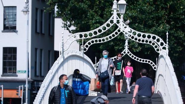 People wearing masks crossing the Ha'penny Bridge in Dublin city centre. Photo: Niall Carson/PA Wire