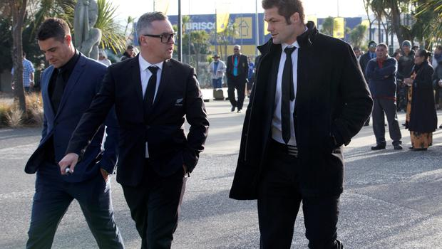 New Zealand All Black rugby union players Richie McCaw, right, and Dan Carter, left, walk with media manager Joe Locke as they arrive for the funeral of former teammate Jerry Collins