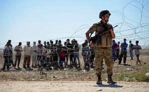 A Turkish soldier stands guard as Syrian Kurds wait behind the border fence near the southeastern town of Suruc in Sanliurfa province. Reuters