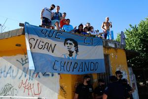 Fans stand on a roof of a house along the way of the motorcade carrying the remains of Diego Maradona to the Jardin de Bellavista cemetery in Buenos Aires, Argentina. (AP Photo/Maria Paula Avila)