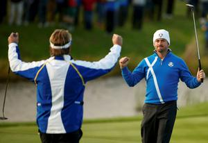 European Ryder Cup players Victor Dubuisson (L) and Graeme McDowell celebrate on the 17th green after winning their foursomes 40th Ryder Cup match at Gleneagles in Scotland