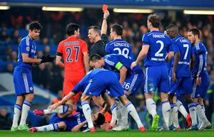 Chelsea players crowd round referee Bjorn Kuipers as he shows a red card to Paris Saint-Germain's Zlatan Ibrahimovic after a clash with Oscar