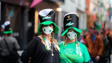 Two women in clover patterned face masks near the Temple bar in Dublin, on St Patrick's day. Photo: Niall Carson/PA Wire