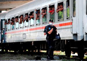 TOPSHOTS Croatian Police stand on the sidings beside a train carrying migrants and refugees in a marshalling yard near Zagreb, on September 18, 2015.  A special train transporting some 1500 migrants from Tovarnik, near the Serbian border, arrived in Zagreb on September 18, 2015. The migrants were being transferred to a reception centre in Zagreb. Since the start of the crisis the Croatian authorities have urged solidarity with migrants, recalling its own role in accommodating hundreds of thousands of refugees and displaced people during the 1990s Balkans wars.   AFP PHOTO / STRSTR/AFP/Getty Images