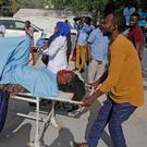 DEADLY ATTACK: The injured are taken to hospital on trolleys after the car bomb at a checkpoint in Mogadishu. Photo: Farah Abdi Warsame/AP