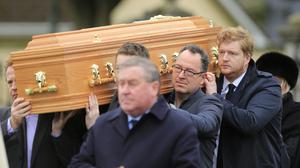 The remains of Marian Finucane are carried in to St Brigids Church by her son Jack (back right).  Picture; Gerry Mooney