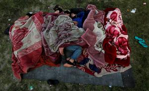 People sleep on the ground in an open area on early morning after an earthquake in Kathmandu, Nepal April 28, 2015. REUTERS/Adnan Abidi