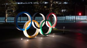 """The Olympic rings stand near the New National Stadium in Tokyo, Tuesday, March 24, 2020. IOC President Thomas Bach has agreed """"100%"""" to a proposal of postponing the Tokyo Olympics for about one year until 2021 because of the coronavirus outbreak, Japanese Prime Minister Shinzo Abe said Tuesday. (AP Photo/Jae C. Hong)"""