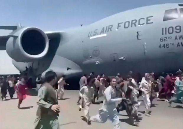 Hundreds of people run alongside a US military plane at Kabul airport