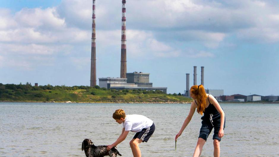 Kids enjoying the fine weather with their dog at Sandymount Strand, Dublin.
