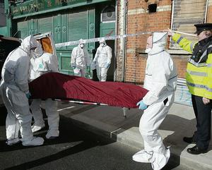 The victim's body is removed from the scene by gardai