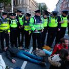 Ring of steel: Gardaí monitor the crowd as Extinction Rebellion demonstrators lie and sit outside Government Buildings on Budget Day in Dublin yesterday.