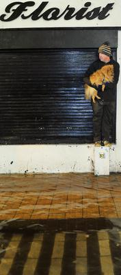 Brendan Cahill takes refuge with dog Paulo during heavy flooding on Oliver Plunkett street, Cork city
