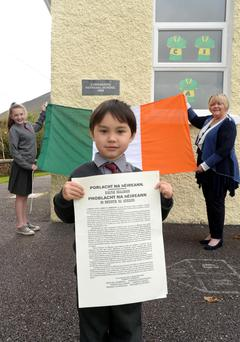 Kevin Walsh (4) the youngest pupil holds the proclamation while Samantha Riordan, (12) the oldest holds the Tricolour with principal Evelyn O'Shea at Curraheen National School, Glenbeigh, County Kerry.