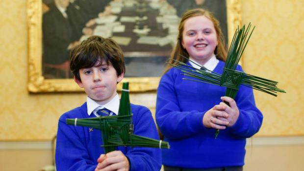 Tradition: Oisín Lee and Sofia Hannon from St Brigid's Primary School, Kildare town, with St Brigid's crosses which they made for President Michael D Higgins at Áras an Uachtaráin last year. Photo by Kenneth O'Halloran