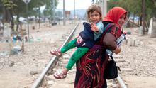 Refugees cross the border line between Greece and Macedonia near the town of Gevgelija
